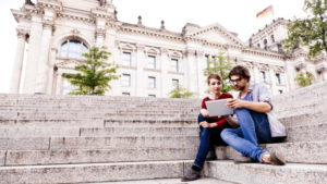 Young couple having fun together with a tablet PC in classical urban surroundings.